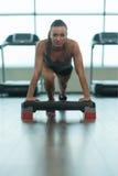 La giovane donna che fare spinge aumenta sul pavimento Fotografia Stock