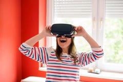 La giovane donna che gode di usare VR googla immagini stock libere da diritti