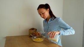 La giovane donna che mangia i fiocchi di granturco con latte per la prima colazione in cucina alla mattina video d archivio