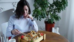 La giovane donna che mangia i sushi arriva a fiumi il ristorante del Giappone stock footage