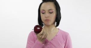 La giovane donna che mangia la mela e dice l'yum La ragazza prende il primo morso e dice vuole mordere video d archivio