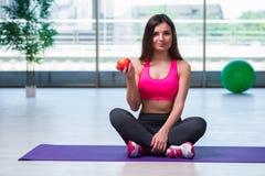 La giovane donna che mangia mela rossa nel concetto di salute Immagini Stock Libere da Diritti