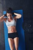 La giovane donna che muscolare fare si siede aumenta su una stuoia di esercizio Immagine Stock Libera da Diritti
