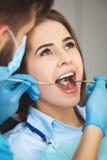 La giovane donna che ottiene i suoi denti ha controllato da un dentista fotografia stock