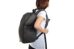 La giovane donna che porta con lo zaino di viaggio ha isolato il backgro bianco Immagine Stock