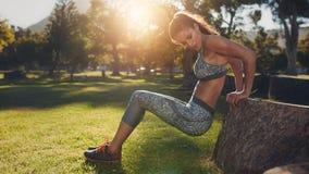 La giovane donna che praticare spinge aumenta in natura Fotografie Stock Libere da Diritti
