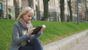La giovane donna che riposa nel parco, gode di una compressa digitale video d archivio