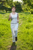 La giovane donna che runing in una sosta ed ascolta musica immagine stock libera da diritti
