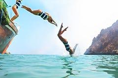 La giovane donna che salta da una barca a vela fotografie stock