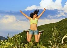 La giovane donna che salta su nelle montagne Immagini Stock Libere da Diritti