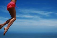 La giovane donna che salta sulla spiaggia tropicale Cielo blu e gambe esili fotografie stock