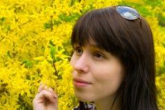 La giovane donna che si leva in piedi ad un albero giallo Immagini Stock