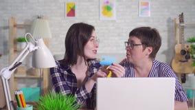 La giovane donna che si siede ad un computer portatile spiega ad una donna di mezza età come usare una carta assegni su Internet stock footage