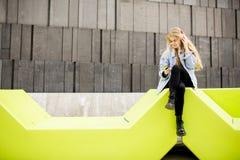 La giovane donna che si siede nella città ed utilizza un telefono cellulare Immagine Stock