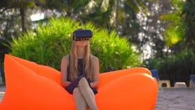 La giovane donna che si siede su un sofà gonfiabile su una spiaggia tropicale usa i vetri di un VR Concetto delle tecnologie mode stock footage
