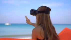 La giovane donna che si siede su un sofà gonfiabile su una spiaggia tropicale usa i vetri di un VR Concetto delle tecnologie mode video d archivio