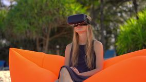 La giovane donna che si siede su un sofà gonfiabile su una spiaggia tropicale usa i vetri di un VR Concetto delle tecnologie mode archivi video