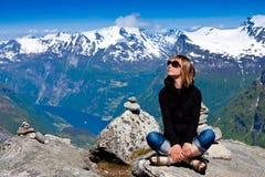 La giovane donna che si siede sulla scogliera e gode della vista Fotografie Stock Libere da Diritti