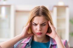 La giovane donna che soffre con il dolore a casa Fotografie Stock Libere da Diritti