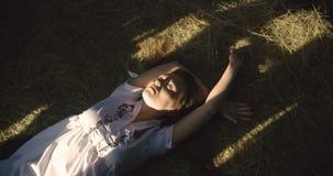 La giovane donna che sorride al sole rays sul fieno Tettoia di legno 4K video d archivio