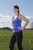 La giovane donna che sta all'aperto su un campo verde nell'allenamento copre Immagini Stock