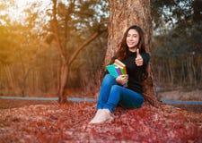La giovane donna che tiene un libro e che mostra il pollice su firma dentro il parco Immagine Stock