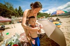 La giovane donna cinese mette sopra suo figlio sulla spiaggia Fotografia Stock