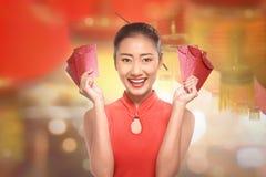 La giovane donna cinese in un cheongsam copre con la busta rossa Fotografia Stock Libera da Diritti