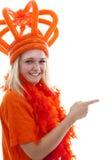 La giovane donna come sostenitore arancio olandese sta mostrando qualcosa Fotografie Stock