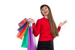 La giovane donna compera con la carta di credito che tiene le sedere di carta multicolori Fotografia Stock