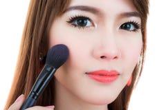 La giovane donna compone con la spazzola cosmetica della polvere Fotografia Stock