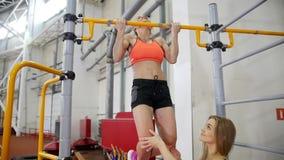 La giovane donna con capelli biondi tira su sulla barra trasversale nella palestra video d archivio