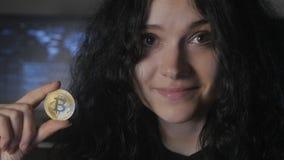 La giovane donna con capelli ricci giudica l'oro Bitcoin disponibile estrazione mineraria e vendere video d archivio