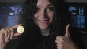 La giovane donna con capelli ricci giudica l'oro Bitcoin disponibile estrazione mineraria e vendere stock footage