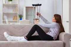 La giovane donna con la gamba rotta a casa Fotografia Stock Libera da Diritti