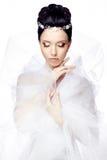 La giovane donna con gli occhi chiusi isolati sul fondo bianco dello studio si è vestita nel capo di organza e di bello diadema Fotografia Stock