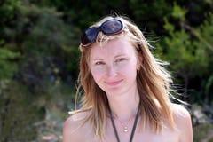 La giovane donna con gli occhiali da sole sta sorridendo Immagini Stock
