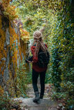 La giovane donna con i dreadlocks biondi con il photocamera osserva la giungla Fotografia Stock