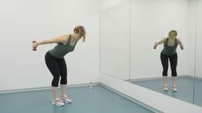 La giovane donna con i dumbells fa gli esercizi per le armi davanti allo specchio archivi video