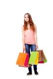La giovane donna con i sacchetti della spesa isolati su bianco Fotografia Stock