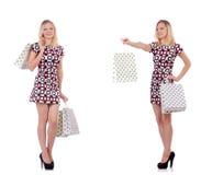 La giovane donna con i sacchetti della spesa su bianco Fotografia Stock