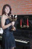 La giovane donna con il candeliere si leva in piedi vicino al piano Immagine Stock