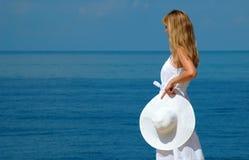 La giovane donna con il cappello bianco esamina il mare Immagini Stock