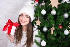 La giovane donna con il contenitore di regalo vicino ha decorato l'albero di Natale Immagine Stock