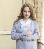 La giovane donna con il fronte con le lentiggini e con il libro in sue mani sta stando l'opposto di una parete grigia fotografia stock libera da diritti