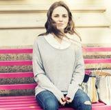 La giovane donna con il fronte con le lentiggini sta collocando su un banco Lunghezza di s dell'immagine all'aperto completamente Immagine Stock