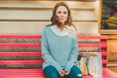 La giovane donna con il fronte con le lentiggini sta collocando su un banco Lunghezza di s dell'immagine all'aperto completamente Fotografie Stock Libere da Diritti