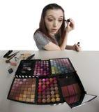 La giovane donna con il vassoio di compone l'applicazione della mascara Fotografie Stock Libere da Diritti