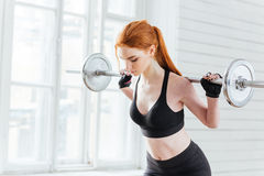 La giovane donna con la bottiglia dell'acqua e gli sport insaccano Immagine Stock