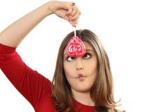 La giovane donna con la lecca-lecca contorce e fa i fronti Immagini Stock Libere da Diritti